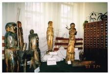 """[Wystawa rzeźby pt. """"Świątki księdza Suwały"""" w Miejskiej Bibliotece Publicznej w Szczytnie]"""