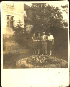 [Trzy kobiety i mężczyzna przed domem]